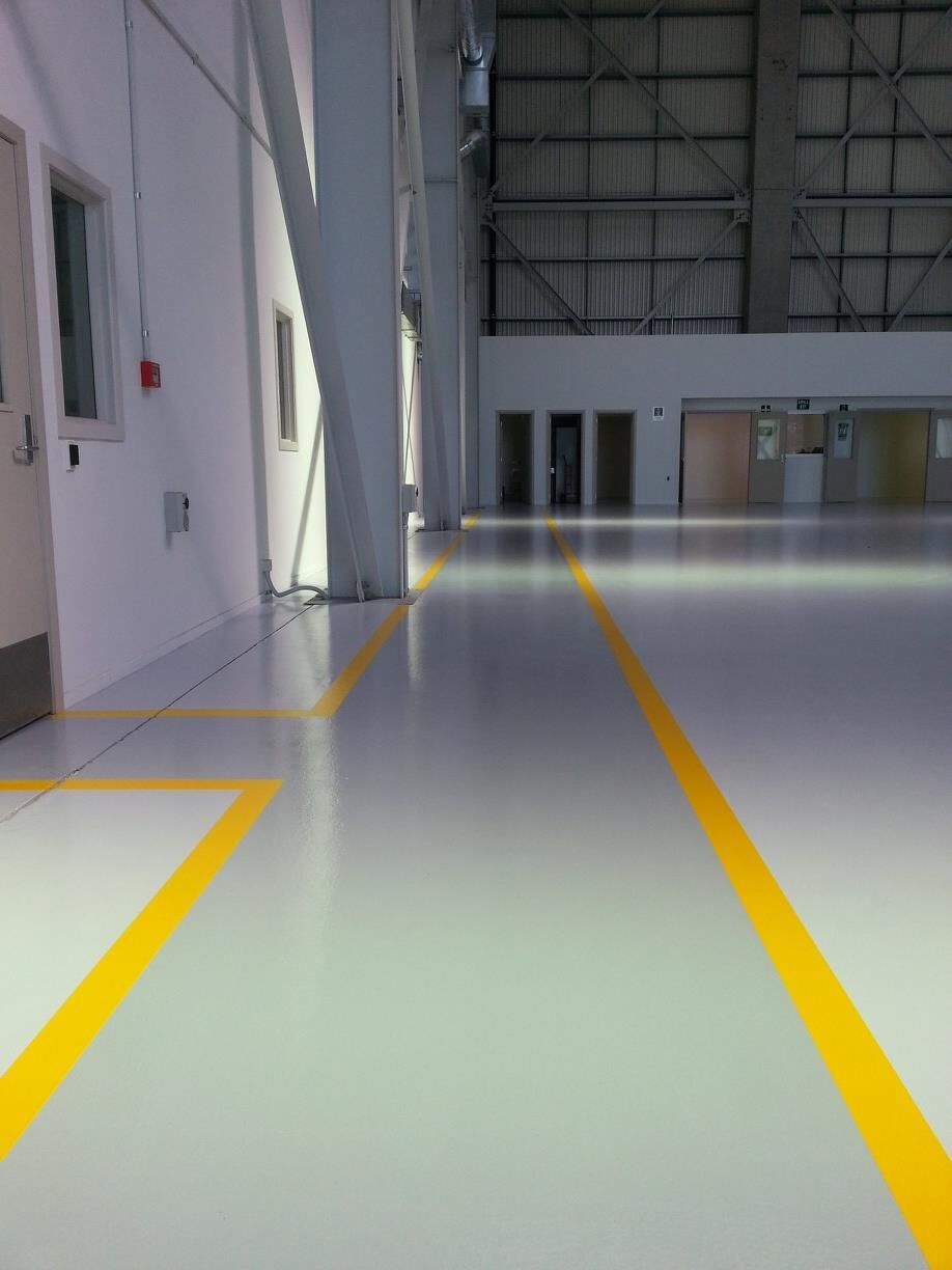 A polished concrete floor with yellow lines on it in a hallway