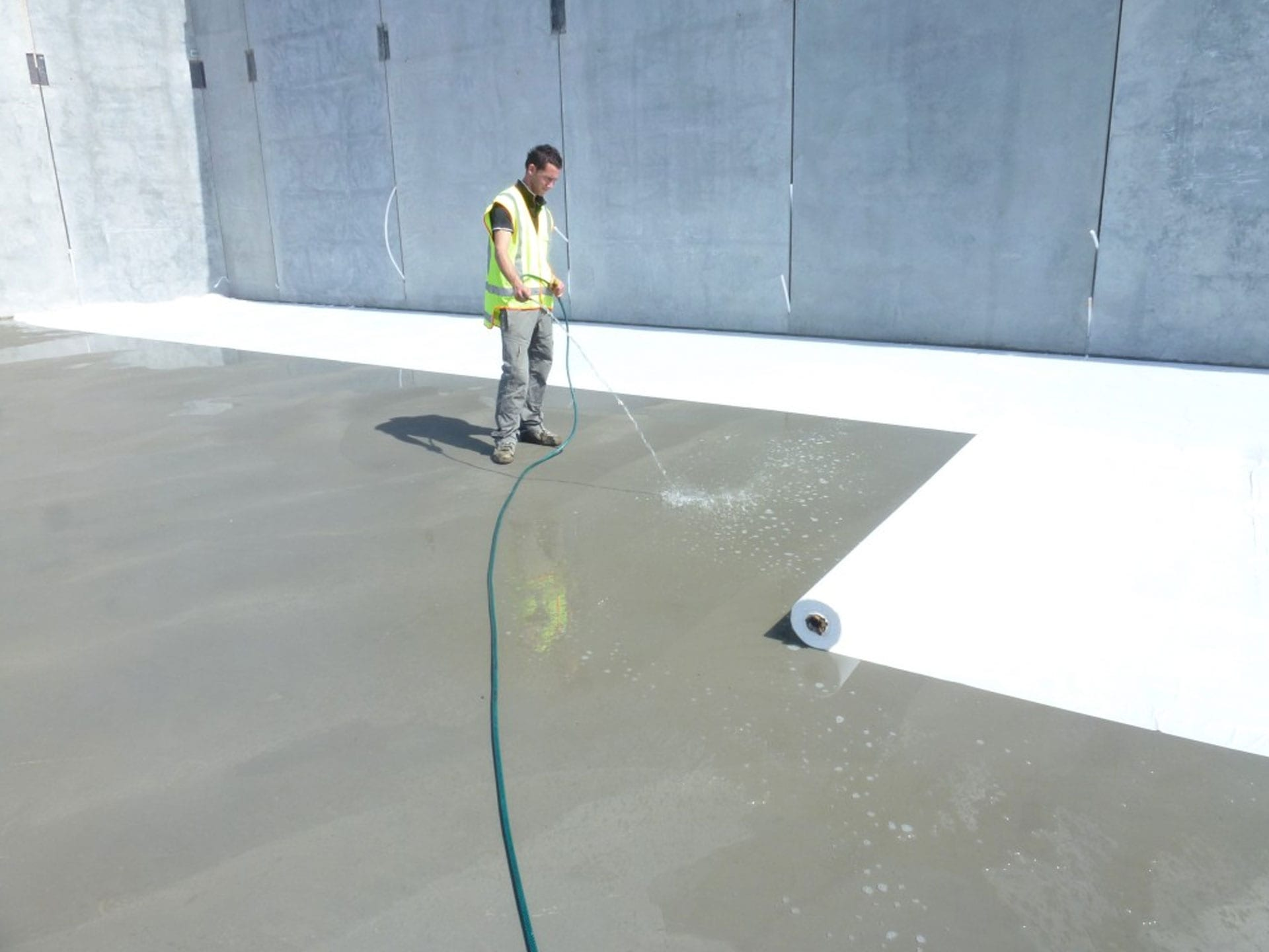 A worker in hi vis curing concrete
